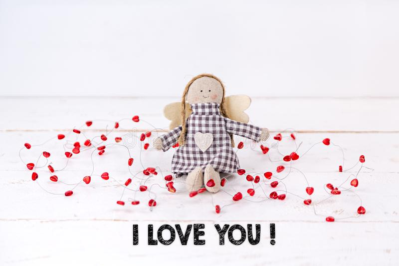 Kleine Marionette mit den roten Herzen 'ich liebe dich ', die sitzen auf einem hölzernen weißen Hintergrund mit dem Text stockfoto