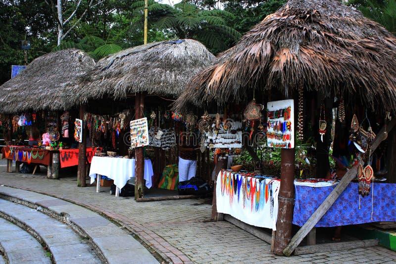 Kleine markt met Inheemse die winkels met daken van bladeren wordt gemaakt die lokale ambachten in Ecuador, Latijns Amerika verko stock afbeelding
