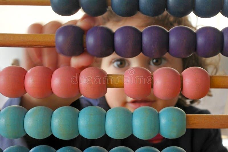 Kleine meid die op Abacus rekent stock afbeeldingen
