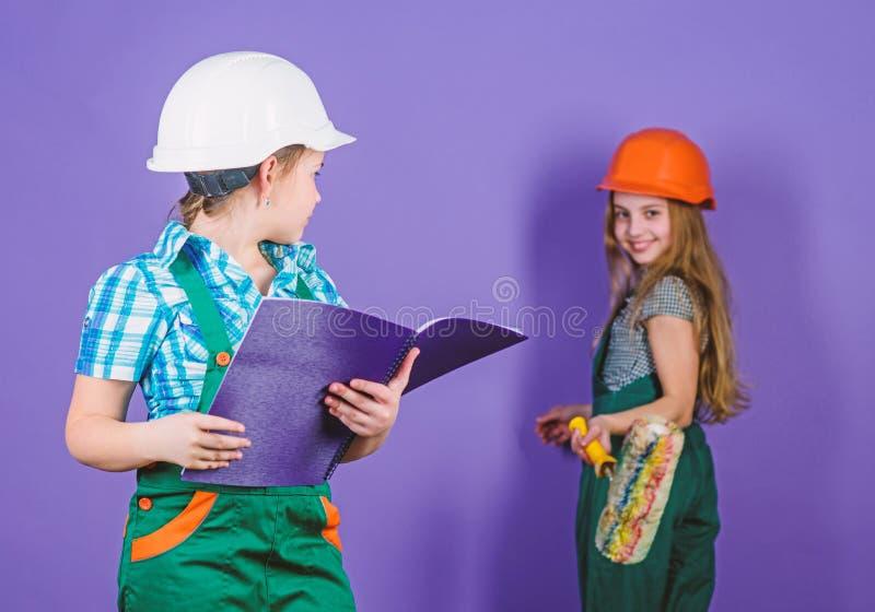 kleine meisjes die samen in workshop herstellen techniekidee Toekomstige carri?re Kleine jonge geitjes in helm met rol arbeid royalty-vrije stock afbeeldingen