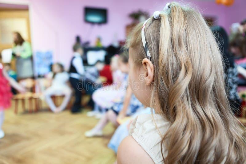 Kleine meisjeszitting in de ruimte van de kleuterschoolklasse bij muziekles stock fotografie
