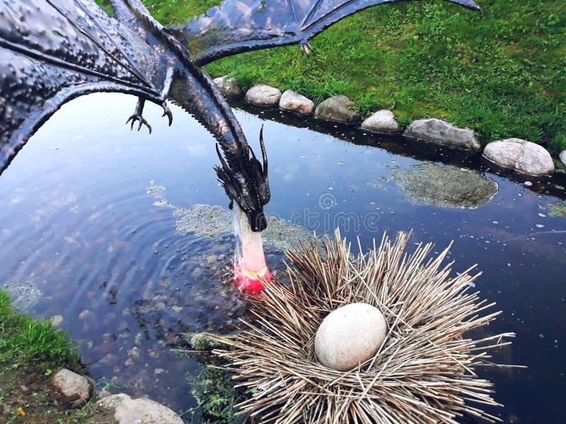 Kleine Metallskulptur eines Fliegendrachen über einem Nest stockbild
