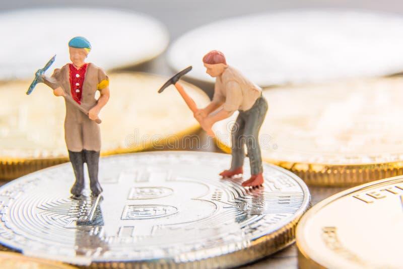 Kleine Miniaturbergmänner, die auf ein bitcoin nahe einen anderen Münzen graben Schlüsselwährungsbergbaukonzept lizenzfreies stockfoto