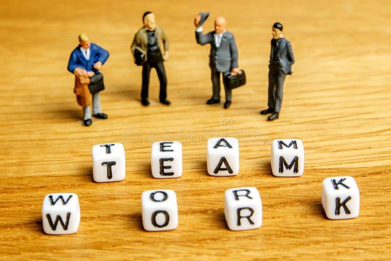 Kleine Miniaturfigürchen mit wenig würfelt die Formung der Wortteamarbeit als Teil Teambesprechungssammlungsbilder stockfoto