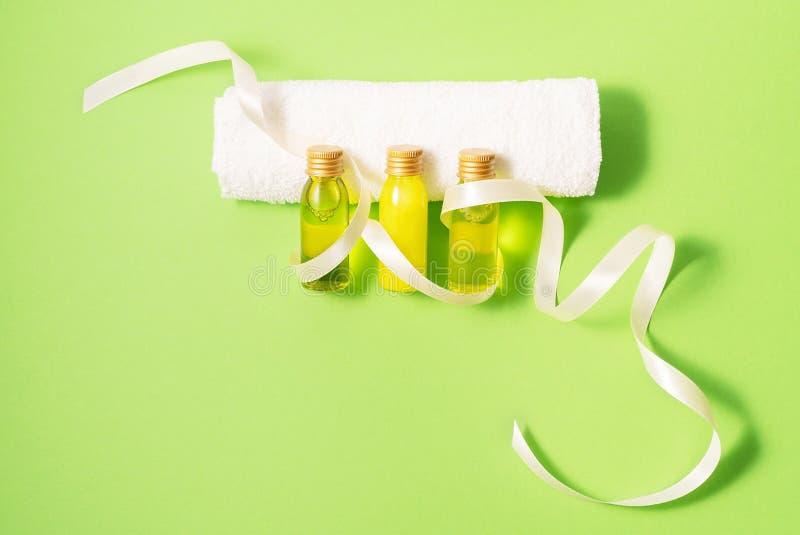 Kleine modelflessen met kuuroordcosmetischee producten met witte handdoek op groene achtergrond Vrouwenschoonheid en schoonheidss royalty-vrije stock foto's