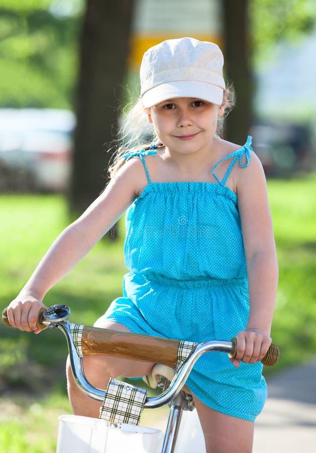 Kleine mooie meisjes berijdende fiets stock afbeelding