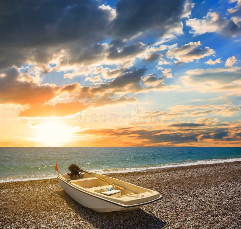 Kleine motorboot op de overzeese kust bij de zonsondergang stock foto's