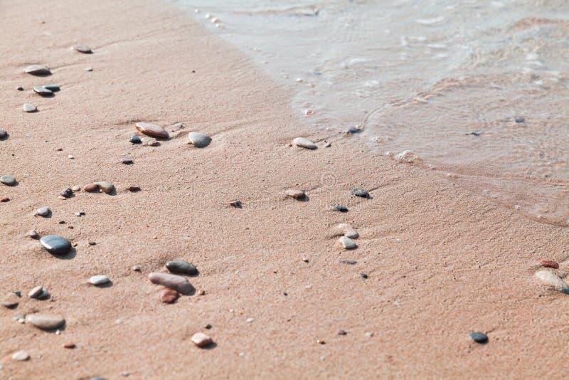 Kleine nass Steine im Sand auf dem Strand lizenzfreies stockfoto