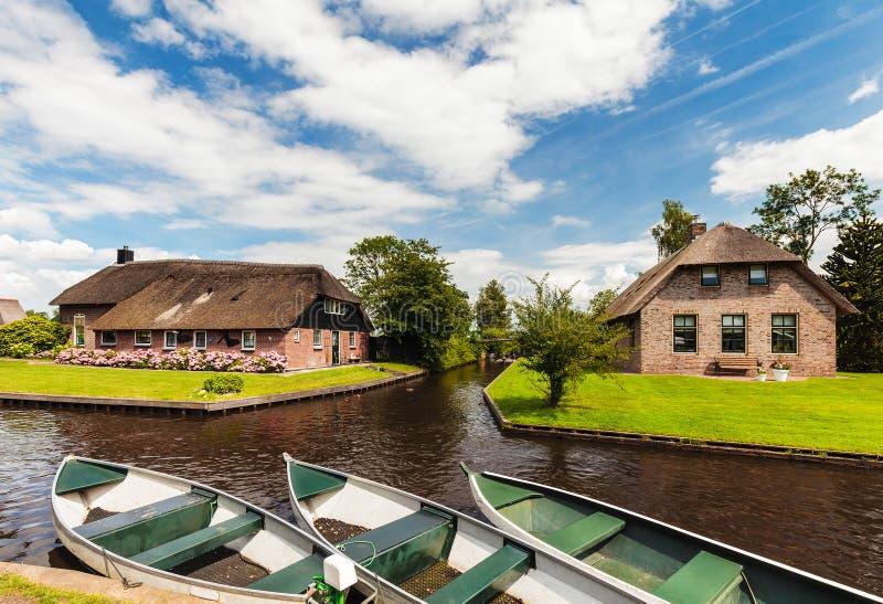 Kleine Nederlandse kanaalschepen voor oude huizen in Giethoorn royalty-vrije stock fotografie