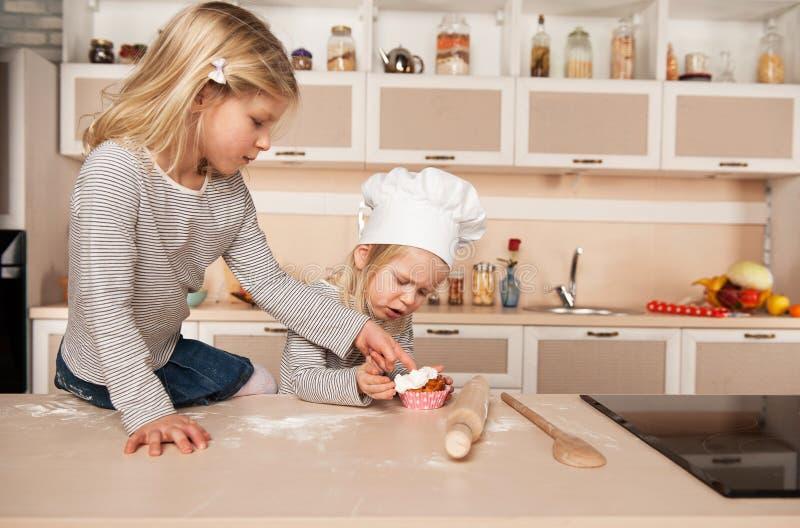 Kleine nette Mädchen, die Kuchen in der Küche schmecken stockfoto