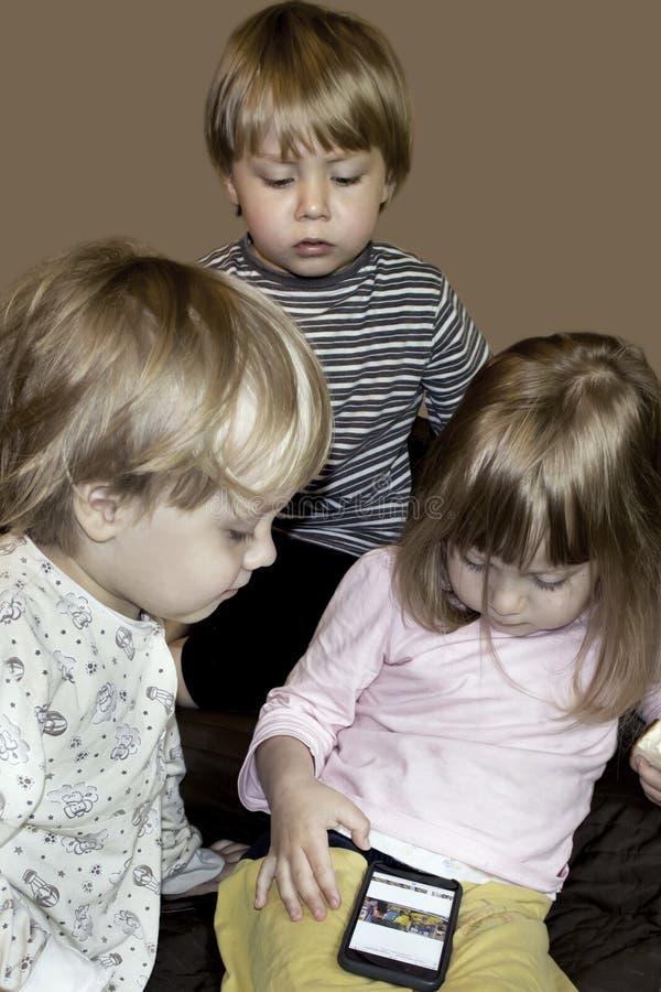 Kleine nette neugierige blonde Dreiergruppen passen Karikaturen auf Smartphone auf stockbild
