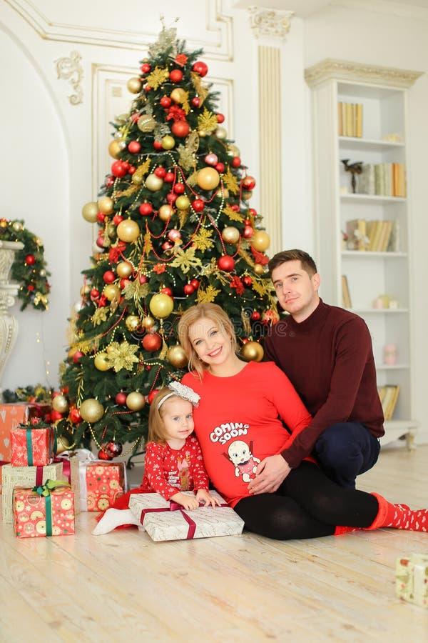 Kleine nette Tochter, die mit Vater und schwangerer Mutter nahe Weihnachtsbaum sitzt und Geschenke hält stockfoto