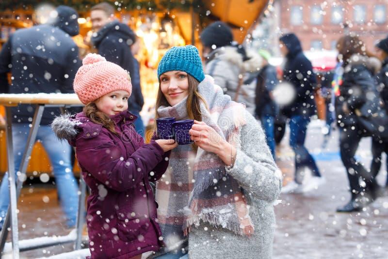 Kleine nette Tochter und Mutter mit Schale dämpfendem heiße Schokoladen- oder Kinderdurchschlag stockbild
