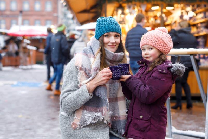Kleine nette Tochter und Mutter mit Schale dämpfendem heiße Schokoladen- oder Kinderdurchschlag Glückliches Kindermädchen und sch lizenzfreie stockbilder