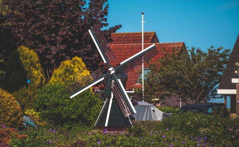 Kleine niederländische hölzerne Mühle im Garten stockfoto