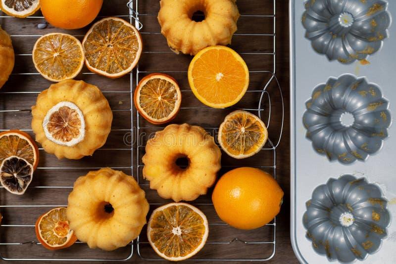 Kleine orange bundt Kuchen mit den frischen und trockenen Orangen auf abkühlendem Ruck, durch die Stützung der Form, Draufsicht,  lizenzfreies stockfoto