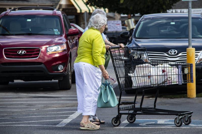 Kleine oude dames in het supermarktparkeerterrein met een boodschappenwagentje en een musicus die voor uiteinden op de achtergron stock foto
