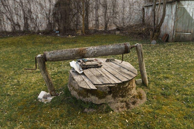 Kleine oude goed houten op gras dichtbij een houten werehouse stock afbeelding