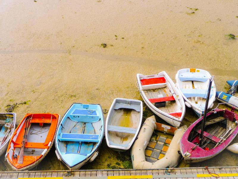 Kleine oude vissersboten op verschillende kleuren die op het strand zijn vastgelopen stock afbeeldingen