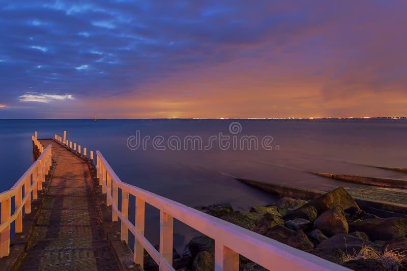 Kleine Pier die in de zonsondergang leiden stock afbeeldingen