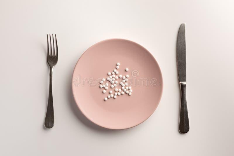 Kleine Pillen auf einer Platte lizenzfreie stockfotografie