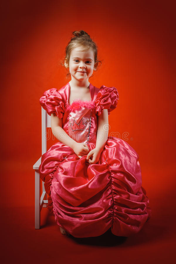 Kleine Prinzessin, die auf einem Stuhl sitzt lizenzfreies stockfoto