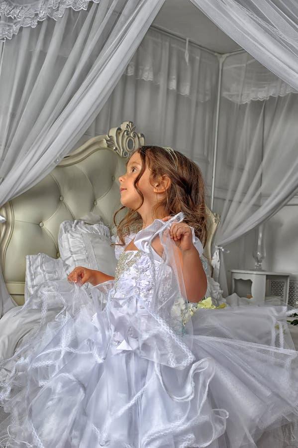 Kleine Prinzessin in einem intelligenten weißen Kleid lizenzfreie stockfotografie