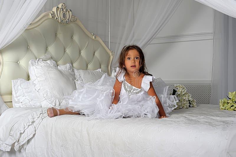 Kleine Prinzessin in einem intelligenten weißen Kleid stockfotos