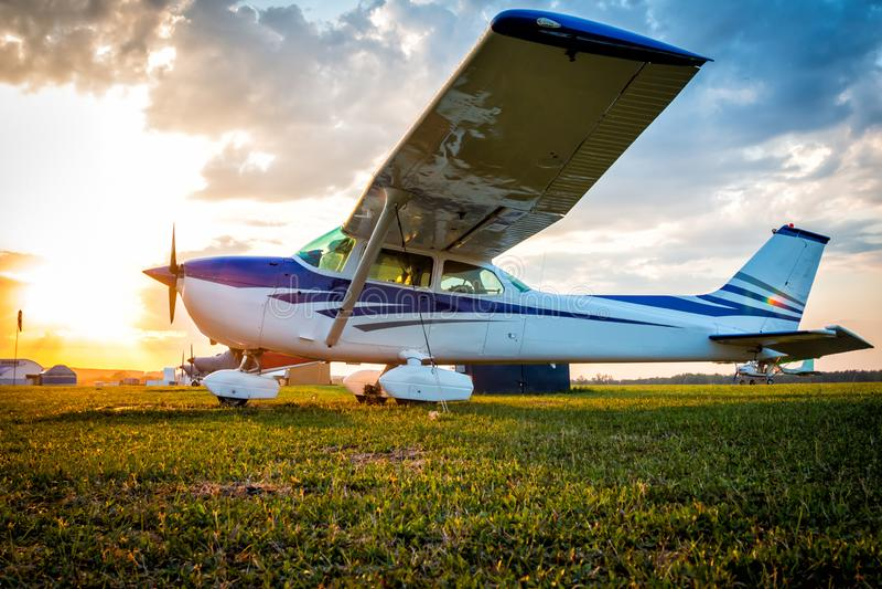 Kleine priv? vliegtuigen op het vliegveld tegen de achtergrond van een kleurrijke zonsondergang stock fotografie