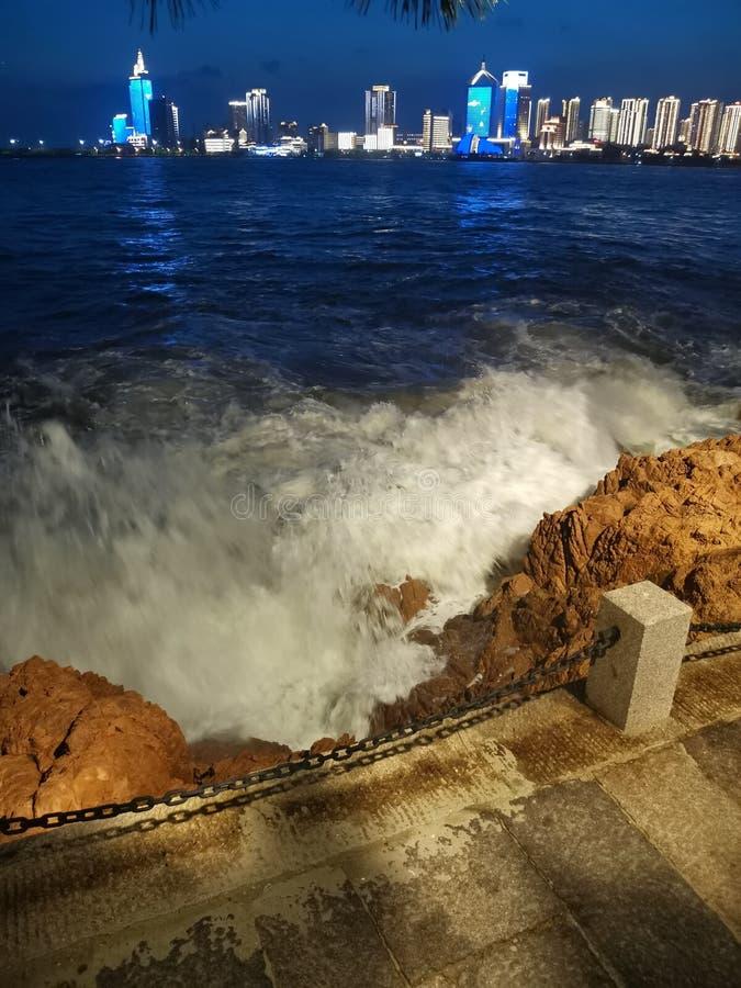 Kleine Qingdao-Parkwellen und entfernte Stadtnachtlandschaft lizenzfreie stockfotografie