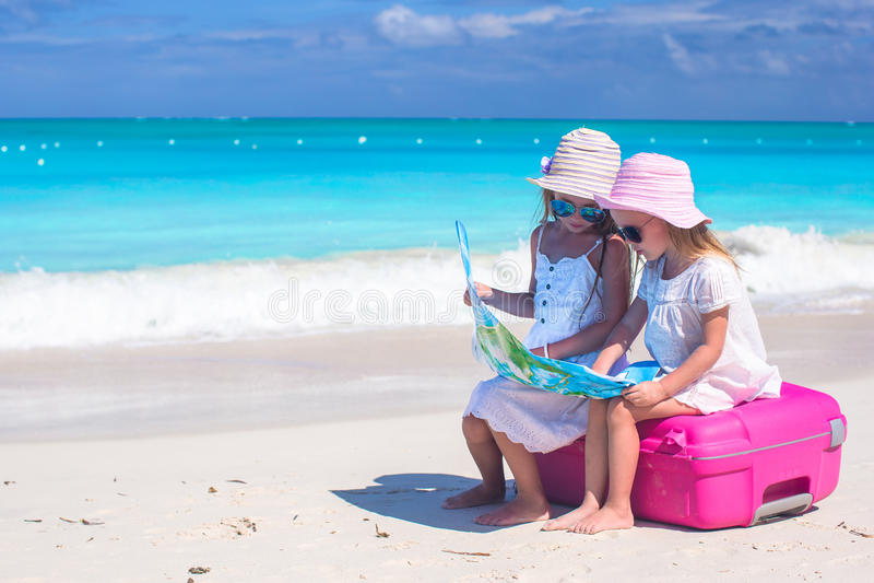 Kleine reizende Mädchen, die auf großem Koffer und einer Karte am tropischen Strand sitzen lizenzfreies stockbild