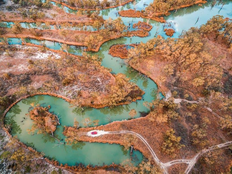 Kleine rode auto aan het eind van landweg op de rand van mooie rivier stock foto's