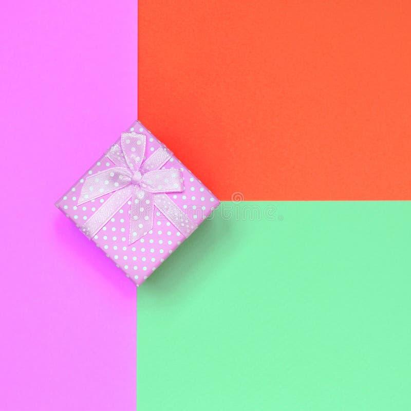 Kleine rosa Geschenkboxlüge auf Beschaffenheitshintergrund des Modepastell-Türkis-, Rotem und rosafarbpapiers stockfoto