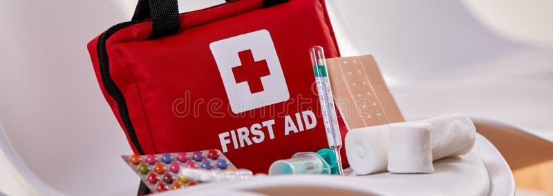 Kleine rote Ausrüstung der ersten Hilfe mit Pillen und Verbänden stockfotografie