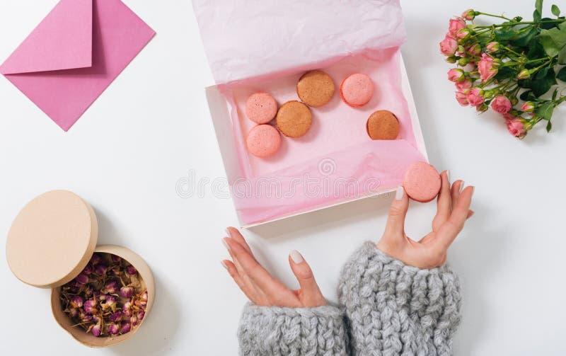 Kleine roze makaron die in handen van een vrouw zijn royalty-vrije stock afbeeldingen
