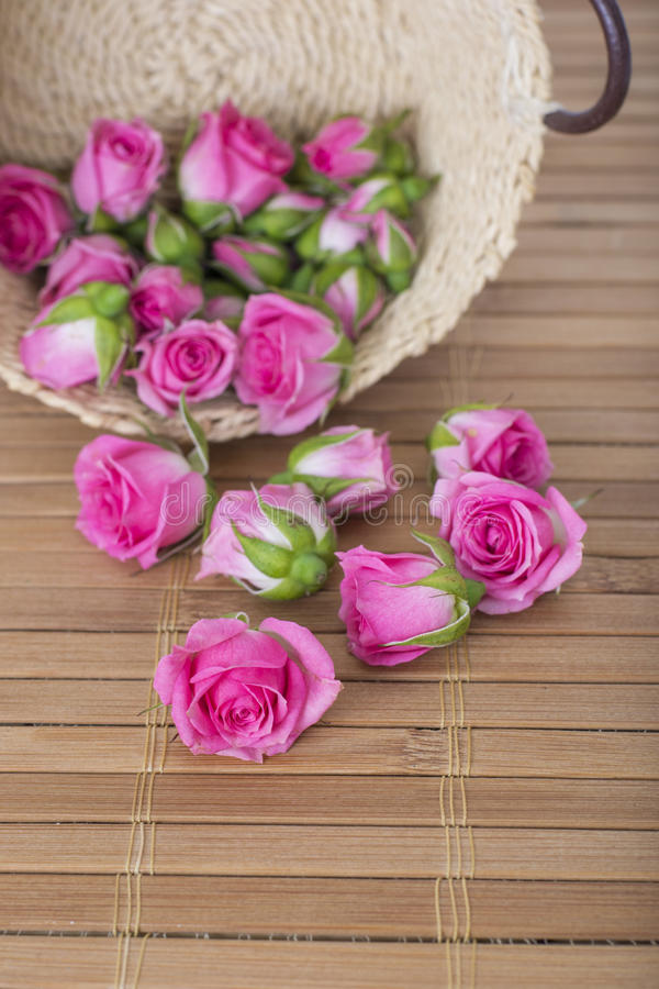 Kleine roze rozen in mand op bamboemat stock afbeelding
