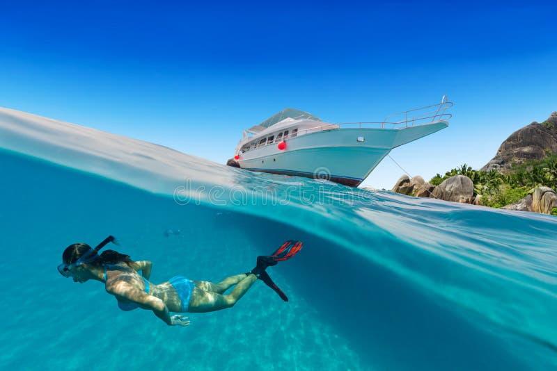 Kleine safariboot die met vrouw onderwater snorkelen stock foto's