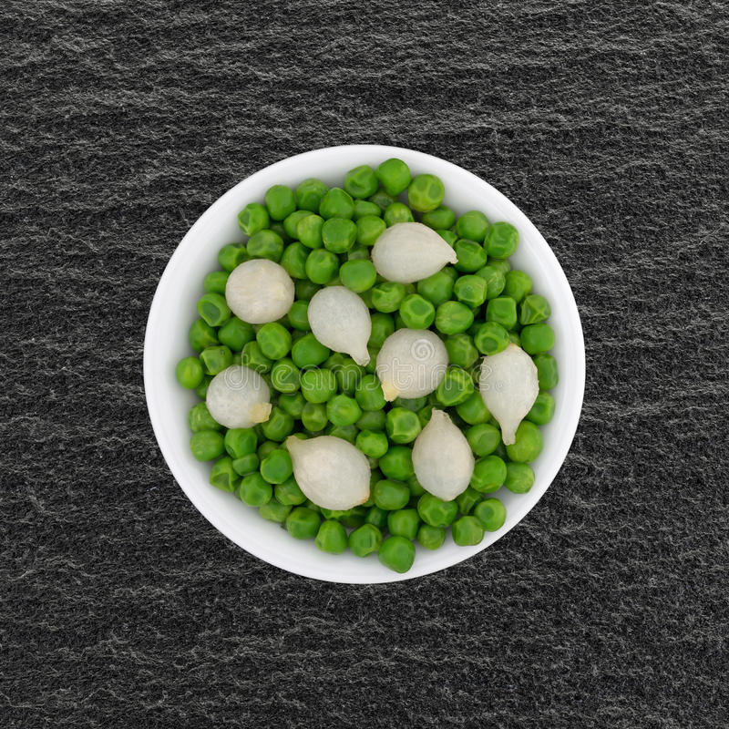 Kleine Schüssel mit gekochten Perlenzwiebeln und grünen Erbsen lizenzfreie stockfotografie
