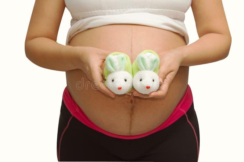 Kleine schoenen voor de ongeboren baby in de buik van zwangere vrouw royalty-vrije stock foto's