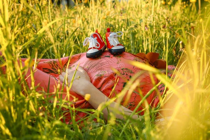 Kleine schoenen voor de ongeboren baby in de buik van zwangere vrouw Zwangere vrouw die het kleine babyschoenen ontspannen houden royalty-vrije stock fotografie