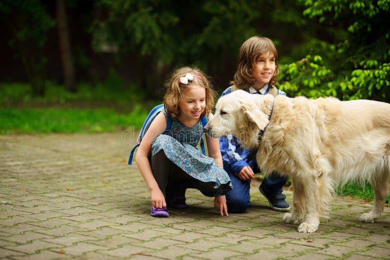 Kleine Schulkinder trafen auf dem Weg zur Schule einen großen Hund stockfotografie