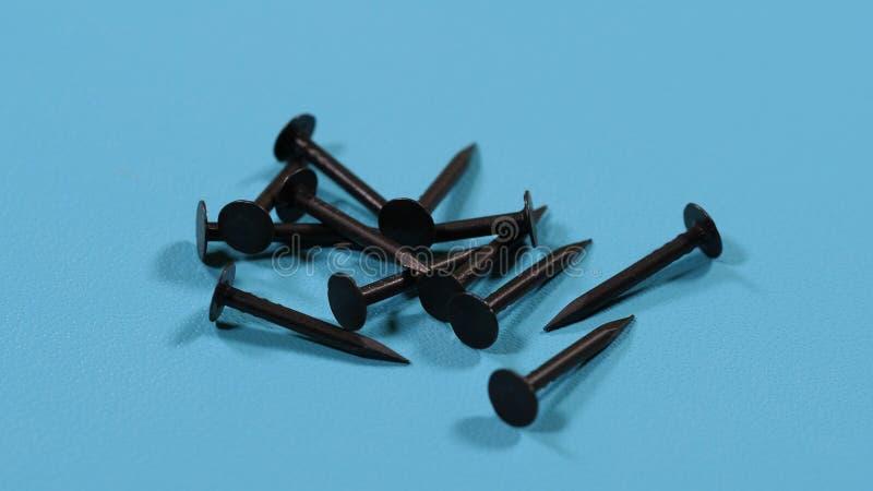 Kleine schwarze Nägel auf einem blauen Hintergrund lizenzfreie stockbilder