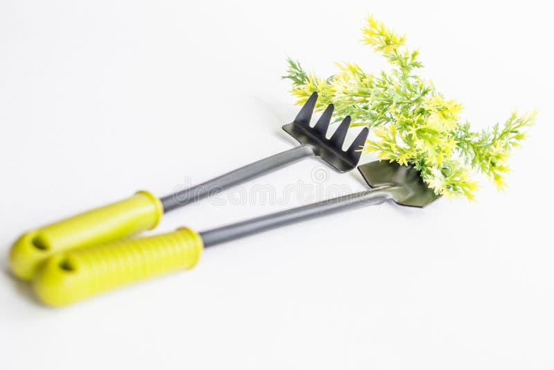 Kleine schwarze Schaufel und Rührstange, gelbgrüne Zweige auf einem weißen Hintergrund stockbilder