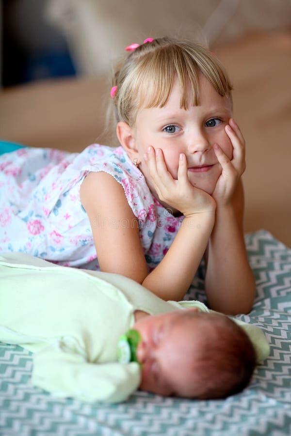 Kleine Schwester, die ihren neugeborenen Bruder umarmt Kleinkindkind, das neue Geschwister trifft  lizenzfreies stockfoto
