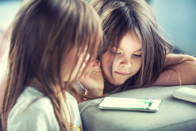 Kleine Schwestern der netten Zwillinge unter Verwendung des modernen smarphone stockfoto