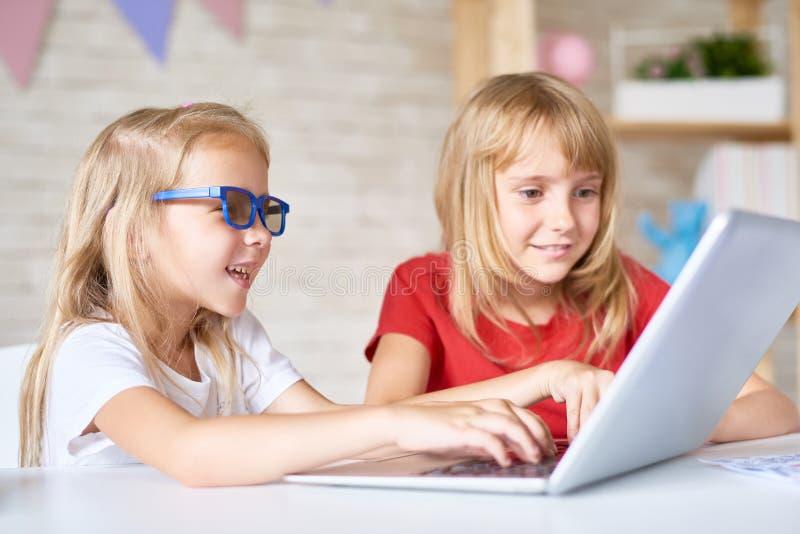 Kleine Schwestern, die Laptop verwenden stockbild