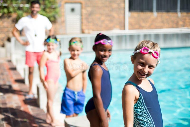 Kleine Schwimmer und männlicher Lehrer, die am Poolside steht lizenzfreie stockbilder