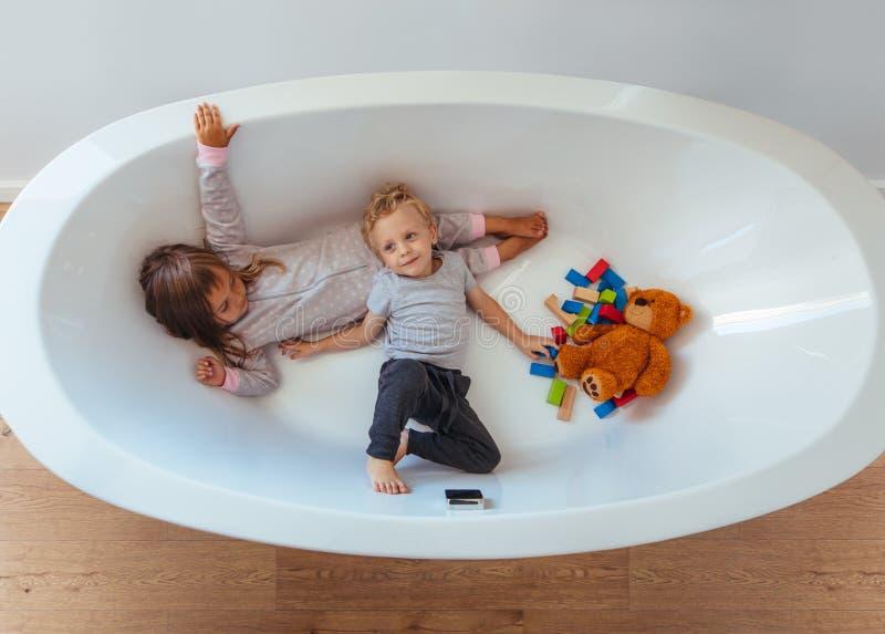 Kleine siblings die binnen een badkuip spelen royalty-vrije stock afbeelding