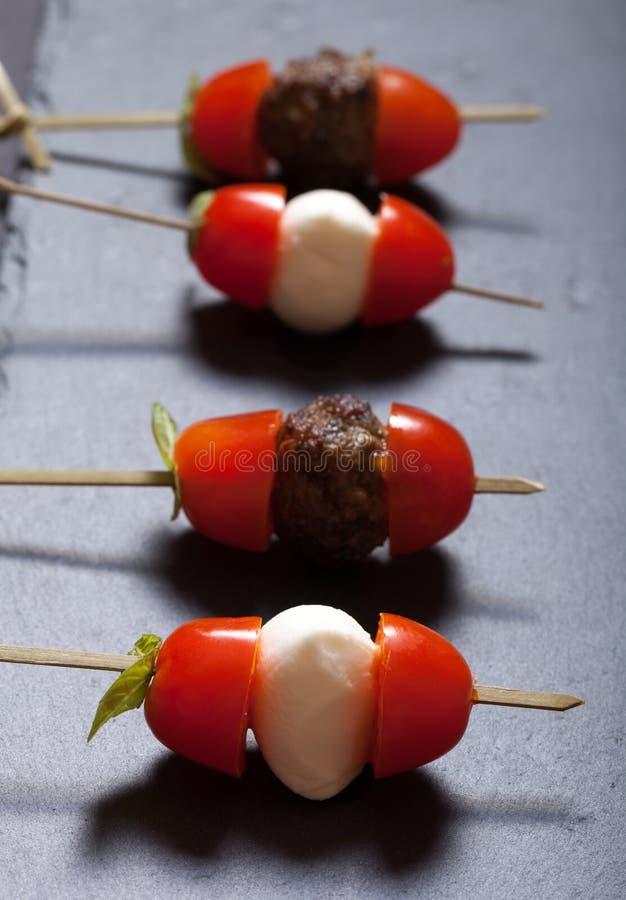 Kleine snacks canape met kersentomaten, mozarella en meatbol stock afbeeldingen