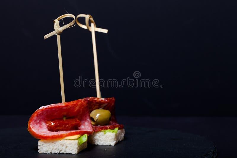 Kleine snacks canape met salami, brood en sla op vleespen  stock afbeeldingen